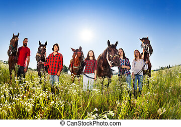 Five happy young people with their horses in field