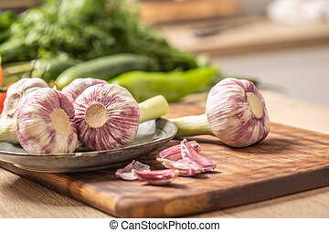 Five heads of garlic on a cutting board with green vegetable in the background