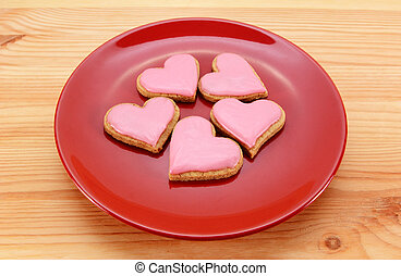 Five heart-shaped iced cookies on a red plate