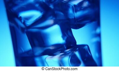 Five ice cubes are shaken in a crystaline glass in the blue...