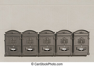 Five metal mailboxes on old italian building