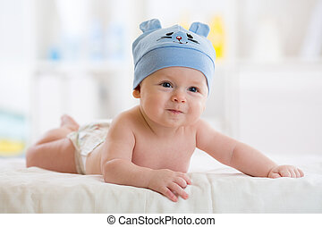 Five months baby boy weared in funny hat lying down on a blanket