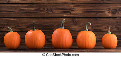 Five orange pumpkins in a row on dark wooden background,...