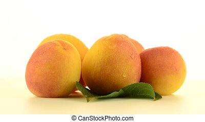 Five peaches rotating on white background.