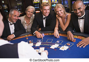 Five people in casino playing blackjack and smiling...