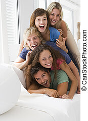 Five people in living room piled up smiling