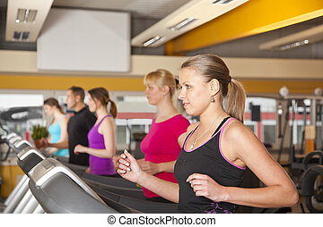 five people running on treadmills - A group of four young...
