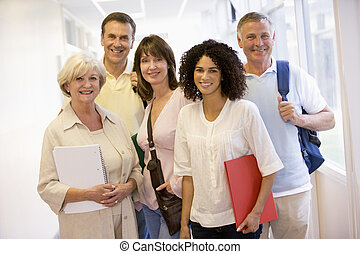 Five people standing in corridor with books (high key)