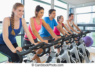 Determined five people working out at spinning class in gym