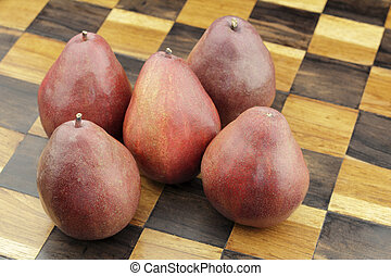 Five Red Pears on a Wooden Chessboard