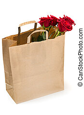 Five red roses in a paper bag on white background
