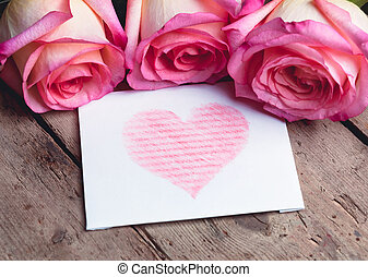 Five roses and white card with a red heart on wooden background.