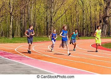 Five running teenage athletes in the stadium
