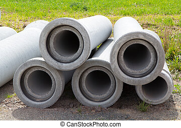 five sewer pipes made ??of concrete lying in the sand