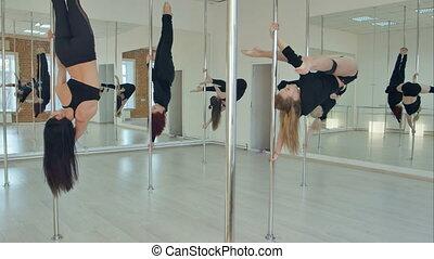 Five sexy slim women team pole dance training in dance hall....