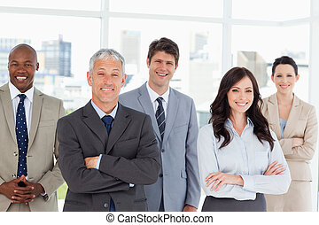 Five smiling business people crossing their arms in front of...