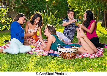 Five smiling friends having drinks in the park - Five ...