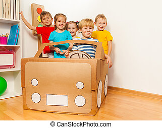 Five smiling kids driving handmade cardboard car