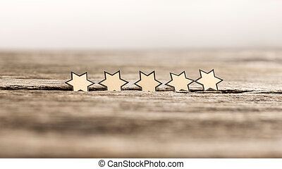 Five stars in a row on a rustic wooden boards