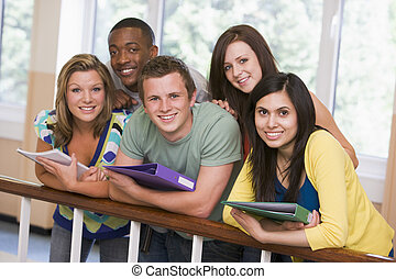 Five students in corridor leaning on railing with notebooks