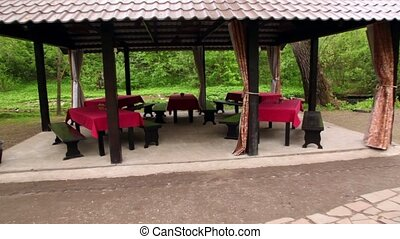 Five tables in bower ashore of small pond at among trees at...