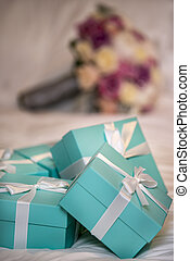 Five Teal Colored Gift Boxes with White Riibbon and Bows on a Bed Comforter