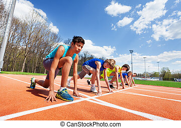 Five teenage athletes ready to run on a racetrack