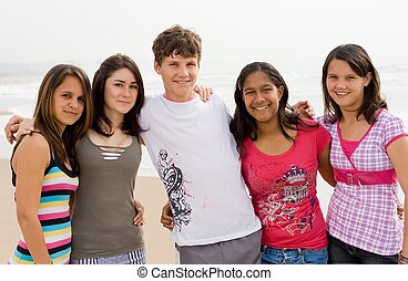 teenagers - five teenagers happily posing together on the...