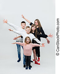 five teenagers with outstretched arms jumping in front of the camera.