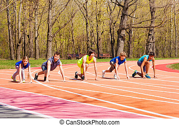 Five teens standing on starting position at track