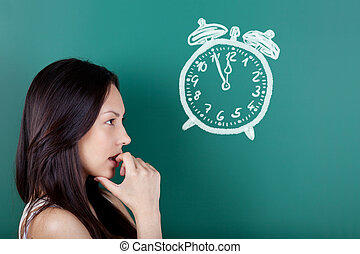 five to twelve - female student looking at a drawn clock...