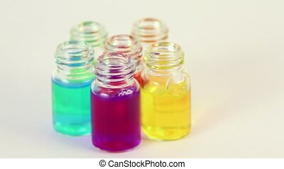 Five transparent bottles spins with color oil on them
