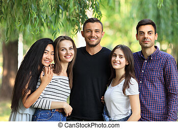 Five women and men friends on green forest background. Half ...