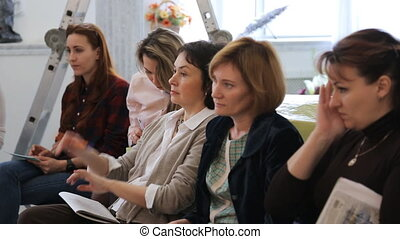 Five women sit on seminar in art studio in day time.