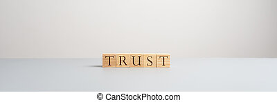 Five wooden blocks with letters spelling the word Trust