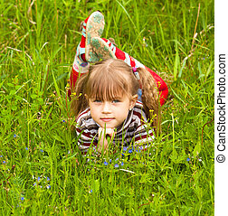 Five-year child lying in grass.
