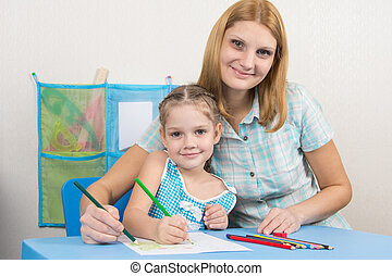 Five-year girl and young mother together paint a picture on a sheet of paper