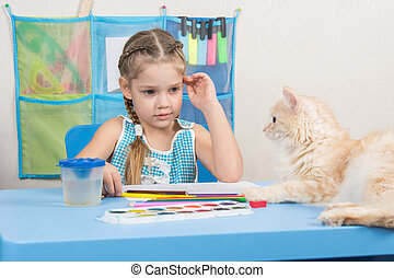 Five-year girl drawing pencils looked at the cat