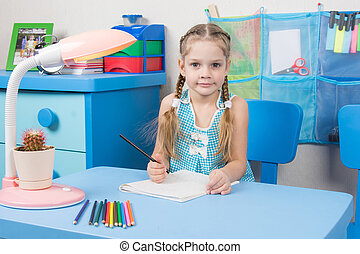 Five-year girl draws pencil in a notebook and looked into the frame