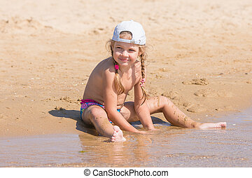 Five-year girl in a cap sits on the sand on beach