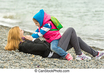 Five-year girl in warm clothes sits astride the mother who is lying on the pebble beach and sea fun looking at each other