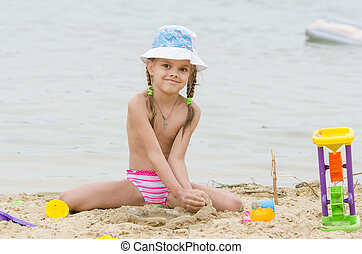 Five-year girl on a river in the sand beach Flashes