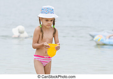 Five-year girl on the beach carrying water in a bucket