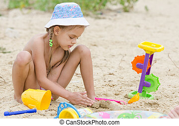 Five-year girl on the river playing in the sand