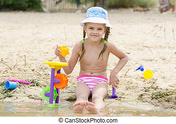 Five-year girl playing on the river sand