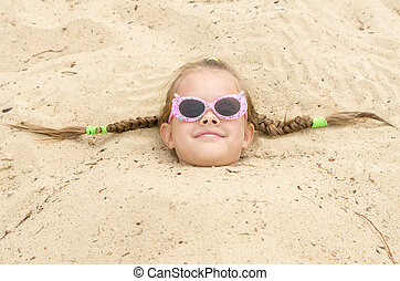 Five-year girl with glasses on the beach