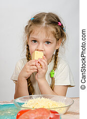 Five-year girl with pigtails eating cheese at the table in front of her is a plate of grated cheese
