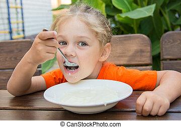 Five-year girl with pleasure eats porridge for breakfast