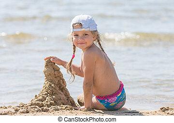 five-year, menina, em, um, boné, senta-se, areia, praia, e, predios, castelo areia