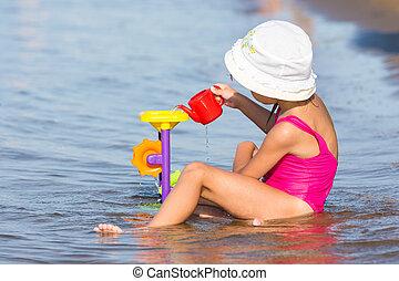 five-year, menina, em, um, cor-de-rosa, fato de banho, sentando, em, ligado, a, banco rio, e, jogos, areia, brinquedos